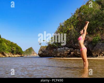 Happy girl in bikini lumineux qui s'étend dans la lagune de la mer. Jeune femme dans l'eau intérieure, l'augmentation des mains vers le haut. Billet de vie, activités de natation Banque D'Images