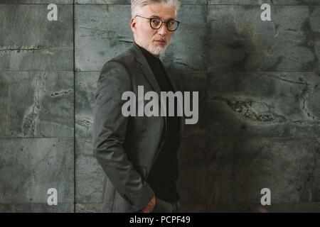 Portrait of businessman standing contre fond gris. Beau mâle debout avec ses mains dans les poches et en regardant la caméra. Banque D'Images