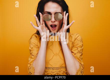 Portrait de beau modèle des femmes portant des lunettes funky. Attractive young woman in robe orange looking at camera avec la bouche ouverte. Banque D'Images