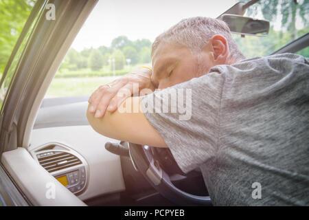 Pilote de l'homme dormir dans la voiture sur le volant Banque D'Images