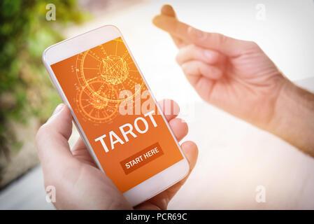 Smartphone avec l'application moderne fortunetelling sur l'écran et la main avec les doigts croisés signe en tant que concept de conseiller psychique ou des derniers moyens de divin Banque D'Images