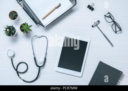 Portrait du médecin de travail avec manuel, stéthoscope, marteau à réflexe et digital tablet on table Banque D'Images