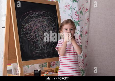 Petite fille d'âge préscolaire l'écriture sur tableau noir. Girl holding craie et dessin. Banque D'Images