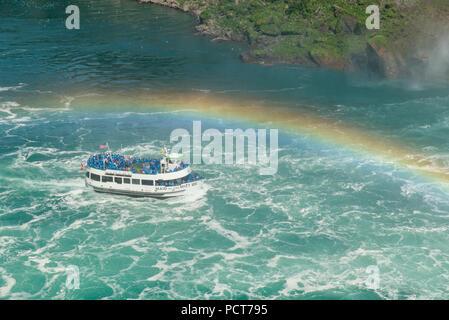 Niagara Falls, Canada et les États-Unis. Excursion en bateau Maid of the Mist sur la rivière Niagara en été sous un arc-en-ciel approcher les chutes canadiennes. Banque D'Images