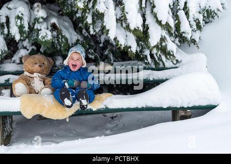 Petit garçon assis avec ours sur un banc et rire dans l'hiver Banque D'Images