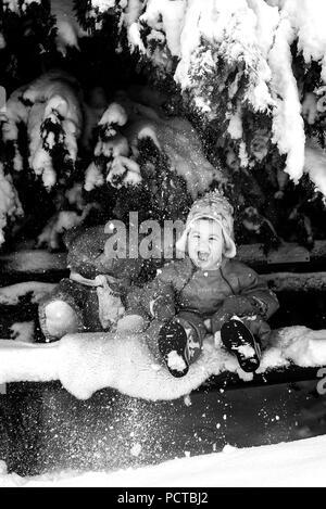 Petit garçon assis avec des ours en peluche sur un banc dans la neige et de rire Banque D'Images