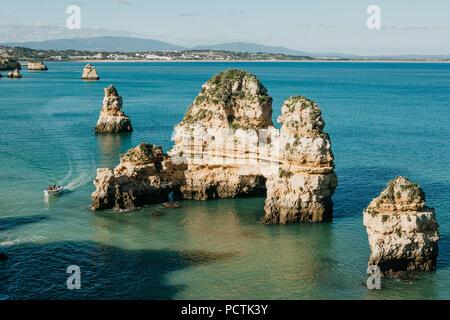 Belle vue sur l'océan Atlantique au large du Portugal, près de la ville de Lagos. Le bateau navigue entre les rochers marins. Banque D'Images