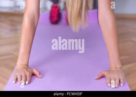 Remise en forme Sport formation femme push up en chambre le tapis de yoga violet. Sport et loisirs concept. Close up, selective focus Banque D'Images