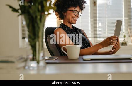 Young smiling woman noir assise à son bureau et regarder l'écran de la tablette numérique dans ses mains. Happy young woman using dig