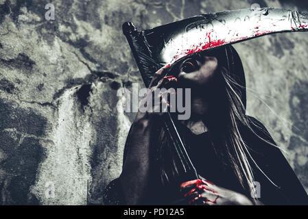 Lécher le sang sur reaper sorcière. Ange démon femelle de noir et le capot sur grunge wall background. Journée de l'Halloween et le mystère concept. Fantasme de m Banque D'Images