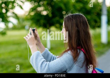 Jeune fille lycéenne en été à l'extérieur. Dans ses mains est titulaire d'un smartphone. Prendre des photos du paysage sur votre téléphone. Photographies en ville. Banque D'Images