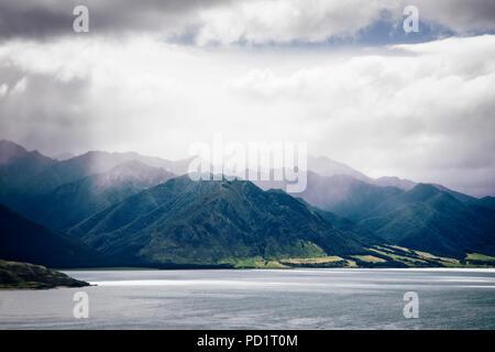 Nuages et soleil sur le lac Hawea, île du Sud, Nouvelle-Zélande.