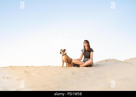 Belle jeune femme à lunettes avec chien assis sur le sable. Fille dans des vêtements de randonnée et Staffordshire terrier puppy sitting sur plage de sable fin ou dans d Banque D'Images