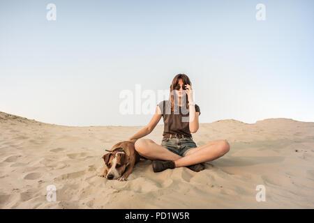 Belle jeune femme à lunettes relève de chien sur une plage de sable ou de désert. Fille dans des vêtements de randonnée et Staffordshire terrier puppy sitting dans Banque D'Images