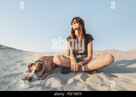 Fille dans des vêtements de randonnée et Staffordshire terrier puppy appréciant chaude journée d'été. Belle jeune femme à lunettes incombe à chien sur sandy bea Banque D'Images