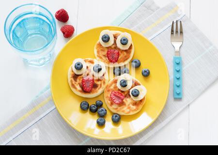 Le petit-déjeuner pour les enfants. Funny face animale des crêpes avec les baies fraîches sur la plaque jaune et verre de l'eau toujours pure. Vue d'en haut Banque D'Images
