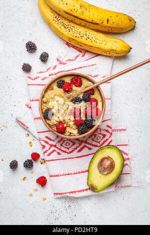Petit déjeuner sain. Bol à smoothie aux fruits rouges. L'avocat de la crème glacée banane vegan aux fruits rouges et muesli dans un bol en bois, vue du dessus. Banque D'Images