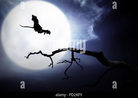 Silhouette de voler avec un balai de sorcière dans la nuit Banque D'Images