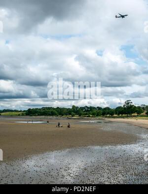 Les promeneurs de chiens sur le sable humide à marée basse avec les frais généraux, l'avion BA Cramond, Édimbourg, Écosse, Royaume-Uni avec British Airways avion volant en ciel Banque D'Images