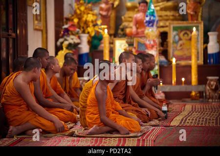 Un groupe de jeunes moines bouddhistes assis sur le sol au cours d'une cérémonie dans l'un des sanctuaires dans leur monastère. À Siem Reap, Cambodge. Banque D'Images