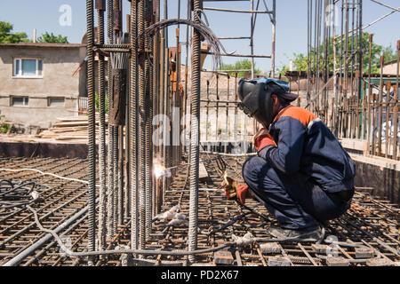 Travailleur de la construction d'armature de métal de soudure pour le déversement de fondation. francs, des personnes réelles