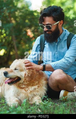 Homme à barbe et son petit chien jaune de jouer et profiter de soleil Banque D'Images