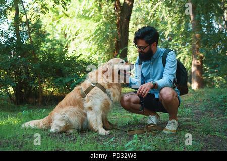 Beau jeune homme avec golden retriver outdoors Banque D'Images