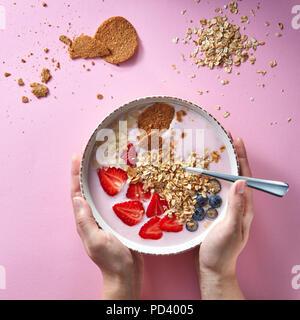En smoothie sain bol blanc avec des fruits naturels, des flocons d'avoine et de biscuits avec woman's hands holding a bowl sur fond rose. De l'air, naturel Banque D'Images
