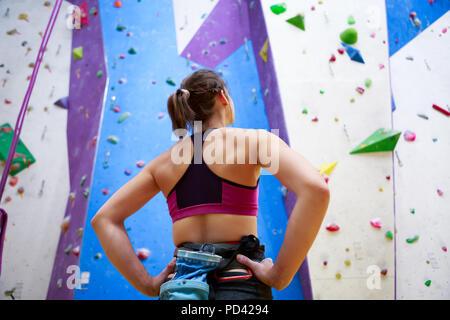Photo de jeune athlète femme de l'arrière avec les mains sur la taille; il est debout à côté de mur pour l'escalade de rocher Banque D'Images