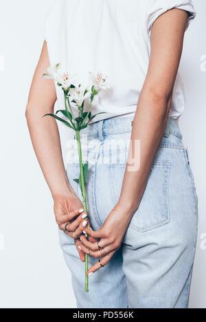 Vue arrière de jeune femme portant un jean boyfriend taille haute tenue brin de lily debout sur fond blanc. Banque D'Images