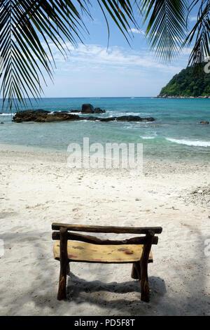Une assise en bois fait à la main à l'ombre des palmiers sur une plage de sable blanc clair avec une petite vague briser, un bleu clair de la mer calme, des rochers sur e Banque D'Images