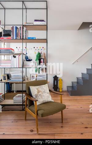 Fauteuil rétro en plan ouvert, espace de vie de famille avec la planche à roulettes et l'unité de rayonnage ouvert Banque D'Images