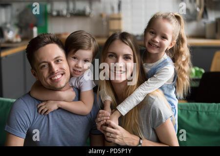 Heureux parents usurpation de son fils et sa fille assis sur le canapé, por Banque D'Images