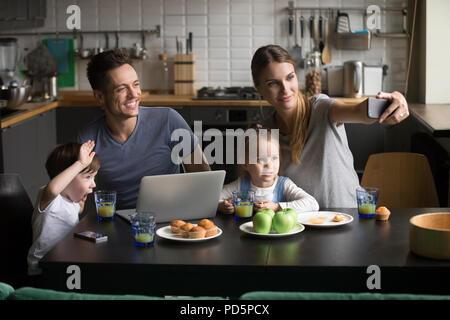 Une famille heureuse avec des enfants en tenant compte de téléphone sur selfies breakfa Banque D'Images