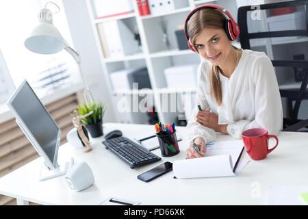 Une jeune fille dans les écouteurs est assis à une table dans le bureau et trace un marqueur sur une feuille. Banque D'Images