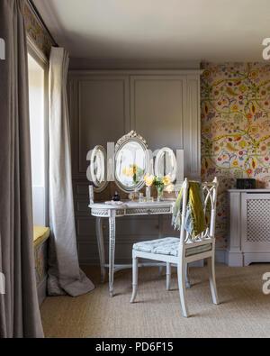 Vintage dressing avec miroir avec chaise à fenêtre dans la lumière. Banque D'Images
