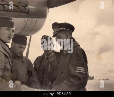 Droit de l'album photo de l'Oberleutnant Oscar Müller de la Kampfgeschwader 1: Le lieutenant Oscar Müller (deuxième à droite) en discussion avec l'Oberleutnant Karl Heinz Müncheberg (à droite) et son équipage, automne 1941. Müncheberg était Staffelkapitän du 5./KG 1 après l'Oberleutnant Clodius a été perdu le 8 novembre 1941. Müncheberg a été abattu par des tirs antiaériens et tués le 17 décembre 1941. Banque D'Images