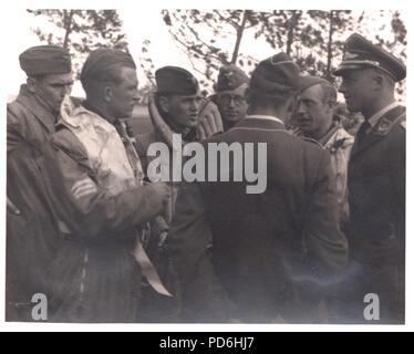 Droit de l'album photo de l'Oberleutnant Oscar Müller de la Kampfgeschwader 1: l'Oberleutnant Friedrich Clodius (deuxième à gauche) en conversation avec son équipage et les officiers du 5./KG 1 à l'été 1941. Le lieutenant Oscar Müller est au centre avec son dos à la caméra. Clodius est le Staffelkapitän du 5./KG 1 durant l'été 1941 et jusqu'à ce qu'il a été affiché le 8 novembre 1941 manquant. Banque D'Images