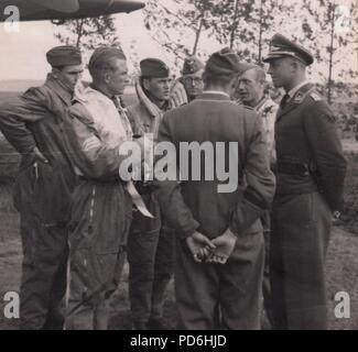 Droit de l'album photo de l'Oberleutnant Oscar Müller de la Kampfgeschwader 1: l'Oberleutnant Friedrich Clodius (deuxième à gauche) en conversation avec son équipage et les officiers du 5./KG 1 à l'été 1941. Clodius est le Staffelkapitän du 5./KG 1 durant l'été 1941 et jusqu'à ce qu'il a été affiché le 8 novembre 1941 manquant. Banque D'Images