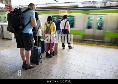 L'île de Honshu, Japon, Tokyo, Kanto, personnes waitng un train sur une plate-forme. Banque D'Images