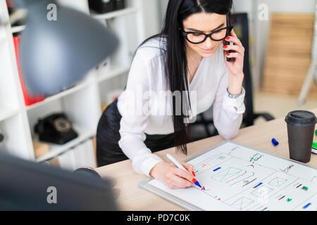 Une jeune fille à lunettes se tient près d'une table, parle au téléphone et trace un marqueur sur un tableau magnétique. Banque D'Images