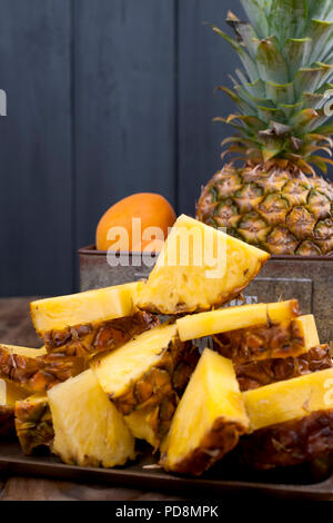 L'ananas et les pêches dans une boîte de métal sur un fond de bois. Vintage photo. Copy space Banque D'Images