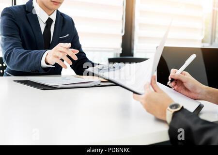 Jeune homme expliquant sur son profil pour les gestionnaires d'affaires assis en entrevue d'emploi. Banque D'Images