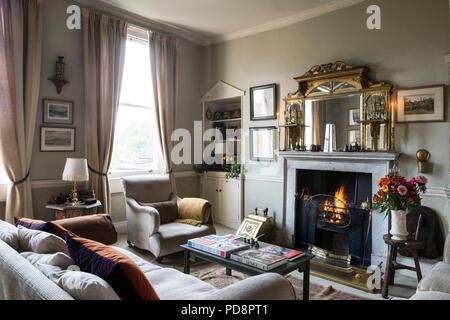 Miroir trumeau doré dans un salon avec fauteuil club, boîte de charbon en laiton de style édouardien et l'aile Banque D'Images