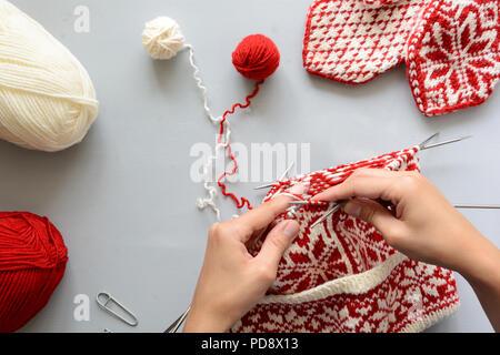 fcea4df093a6 ... Tricot fille jacquaed rouge et blanc aiguilles à chapeau gris sur fond  de bois. Processus