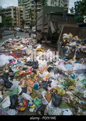 Des sacs en plastique remplis de déchets ménagers se trouvent sur rue à côté de poubelle à Mumbai, Inde