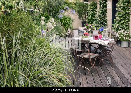 Chaises de bistrot ancien français autour de longues tables en bois sur un toit-terrasse avec meubles de jardin. Agapanthus et Jasmine s'épanouit dans l'arrière-plan Banque D'Images