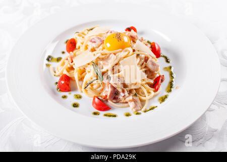 Spaghetti Carbonara. Les pâtes italiennes sur plaque blanche avec le parmesan, jambon et œuf Banque D'Images