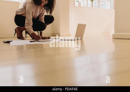 Femme entrepreneur en tenue de prendre des notes tout en travaillant sur un ordinateur portable à la maison. Businesswoman sitting on floor portaient des sandales à la maison maki Banque D'Images