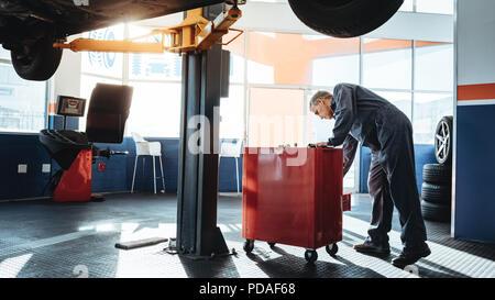 Travail de mécanicien dans le garage et vous recherchez des outils dans la boîte à outils. Réparateurs travaillant en station-service. Banque D'Images